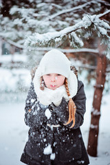 cute happy child girl blowing the snow in winter forest