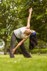 Relaxed brunette doing yoga on grass