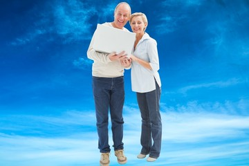 Composite image of mature couple smiling at camera with laptop