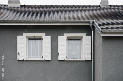 holzfenster mit wei en pvc klappl den in grauer fassade. Black Bedroom Furniture Sets. Home Design Ideas
