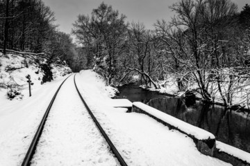 Snow-covered railroad track and creek in rural Carroll County, M