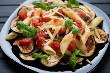 Black glass plate with pasta alla Norma, close-up, studio shot