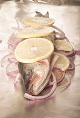 Fish prepared for roasting on the foil with lemon and onion.tint