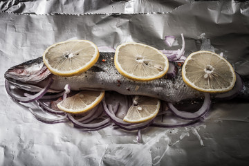 Fish prepared for roasting on the foil with lemon and onion