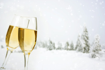 Glasses with champagne on winter background