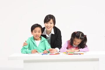 그림 그리기를 가르쳐주는 여선생님과 두 아이