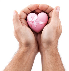 Pink heart in male hands.