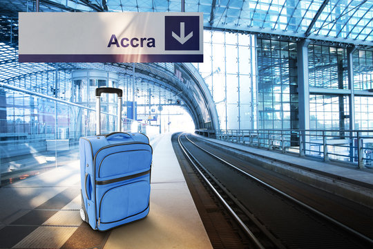 Departure for Accra, Ghana. Blue suitcase at the railway station