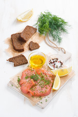 appetizer - salted salmon, bread and ingredients on board
