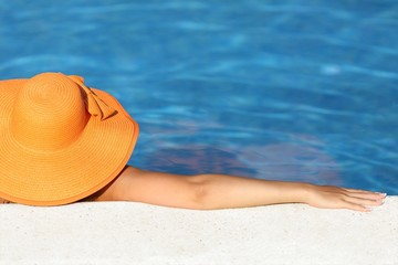 Woman with picture hat bathing relaxed in a pool