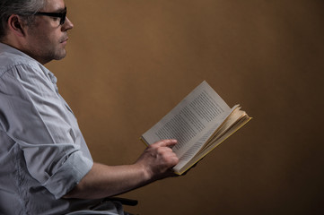 Man sitting in chair and reading book.