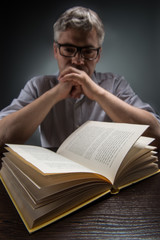 Man sitting at brown table and reading book.