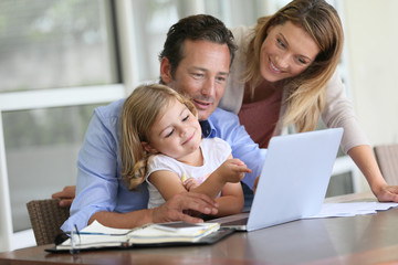 Parents with little girl looking at pictures on computer