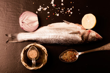 Fresh sea fish lying on dark background with spices