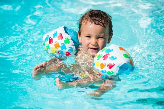 petit garçon avec brassards dans l'eau