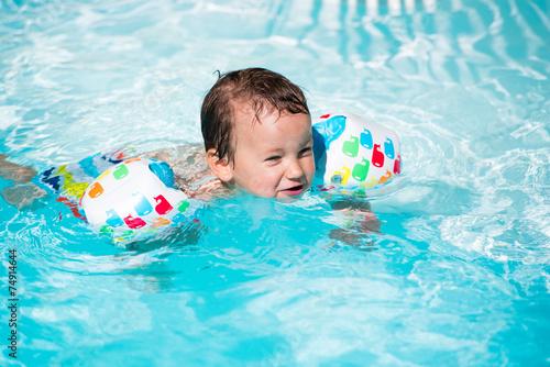 Enfant avec brassards dans une piscine photo libre de for Brassards piscine