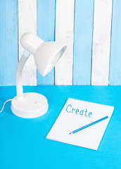 White lamp on blue and white background with note