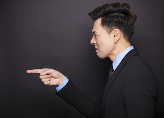 side view angry businessman standing before black background