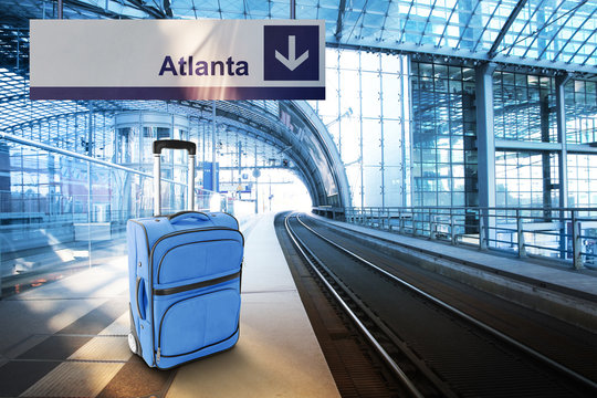 Departure for Atlanta. Blue suitcase at the railway station