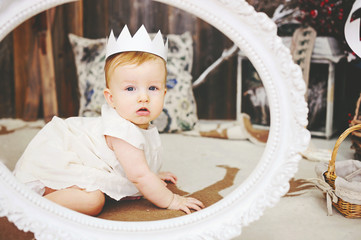 Portrait of a cute baby girl with paper crown