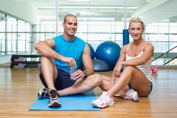 Fit couple sitting on floor at fitness club