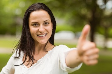 Positive casual brunette with thumbs up