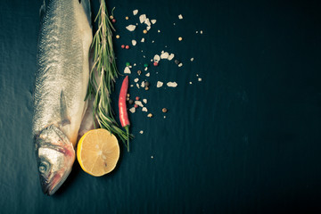 Fresh sea fish lying on dark background with spices. Space for t