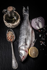 Fresh sea fish lying on dark background with spices. tinted