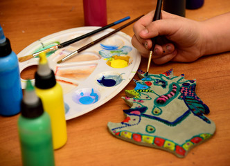 Girl paints a clay toy.