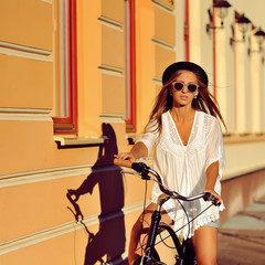 Hipster girl on a vintage bicycle - outdoor fashion portrait