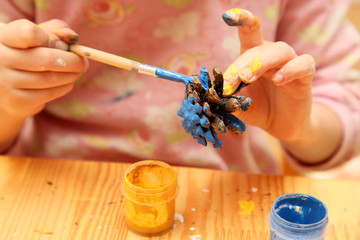 The child painting pinecone in blue colour