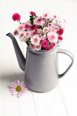 Beautiful flowers in pitcher on table close-up