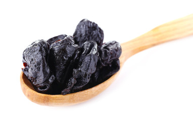 Wooden spoon of prunes isolated on white