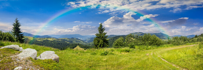 boulders on hillside meadow in mountain with rainbow