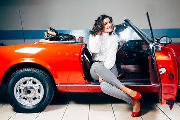 Beautiful young woman sitting on a red vintage car