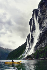 kayaker takes a foto of huge waterfall, Geiranger, Norway