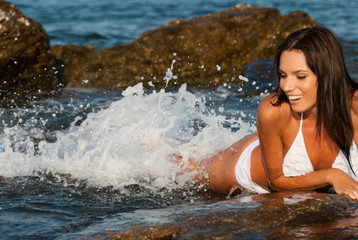 Beautiful young model posing on rocks in sea water