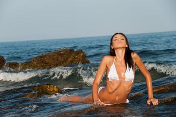 Beautiful young Greek model posing on rocks in sea water