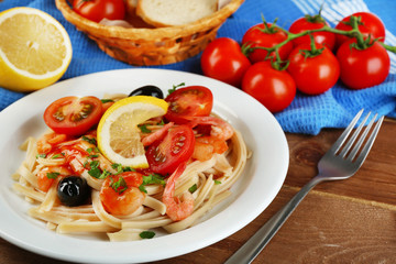 Tasty pasta with shrimps, mussels, black olives and tomato