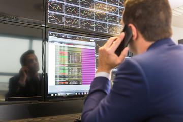 Stock trader looking at computer screens.