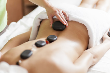 Young woman having a hot stone massage therapy