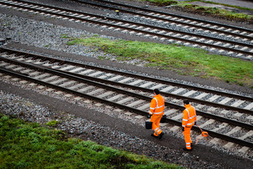 Two workers walking along railroad tracks