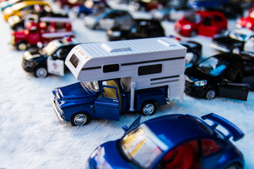 Toy cars are placed in rows for sale with a truck,