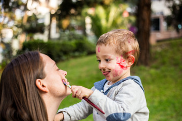 Happy child painting his mother´s face in the park