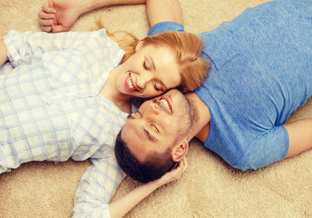 smiling happy couple lying on floor at home