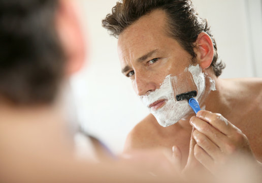 Mature handsome man shaving in front of mirror