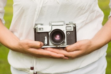 Mid section of woman holding retro camera