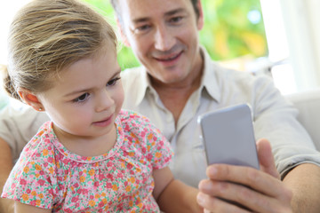 Little girl looking at daddy's smartphone