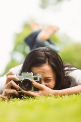Brunette lying on grass with retro camera taking picture
