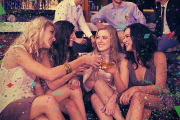 Composite image of pretty friends having a drink together